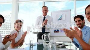 Business manager applauding his staff at meeting