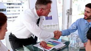 Business manager talking to staff during meeting and shaking hands
