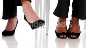 Businesswomen shaking their feet nervously