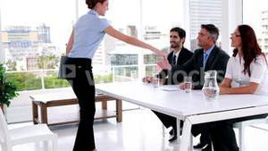 Interview panel speaking with young applicant and shaking her hand