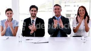 Interview panel applauding the camera