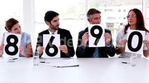 Interview panel holding up scores