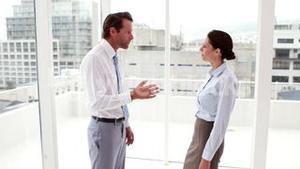 Business team arguing by large window