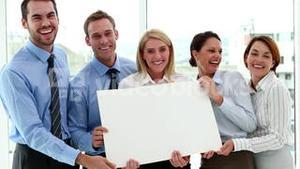 Happy business team showing a white card