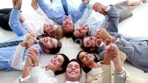Business people lying in a circle holding hands