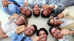 Business people lying in a circle showing thumbs up