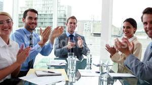 Business people clapping at camera in board room