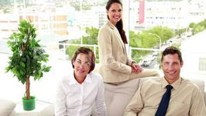 Business people sitting on couch smiling at camera