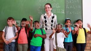 Pupils and teacher waving and smiling at camera in classroom