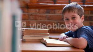Little boy reading book in classroom