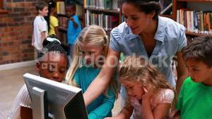 Pupils looking at the computer in library with their teacher