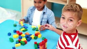 Cute little boys playing with building blocks at table