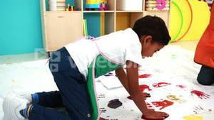 Cute little boys hand painting on white paper in classroom