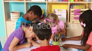 Preschool class drawing at table in classroom