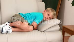 Sad little boy lying on the couch
