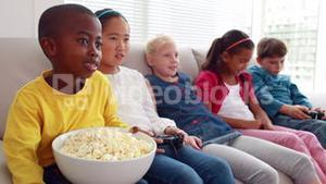 Cute children playing video games on the sofa