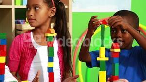 Cute classmates playing with building blocks