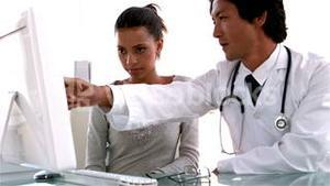 Doctor explaining something on computer to patient