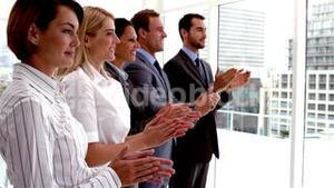 Team of business people clapping in a row