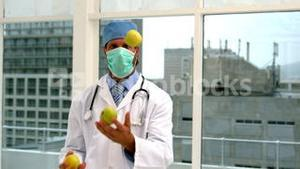 Doctor in mask juggling green apples