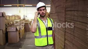 Warehouse worker talking on the phone looking around