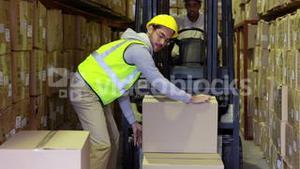 Warehouse worker packing boxes on forklift