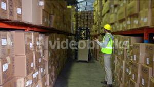 Warehouse worker directing forklift driver