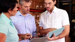 Warehouse operatives discussing file on tablet pc