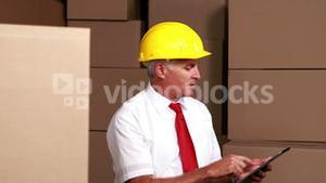 Warehouse manager sitting using his tablet pc
