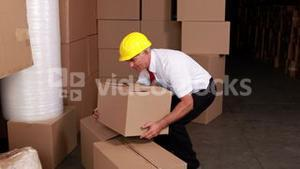 Warehouse manager injuring his back moving boxes