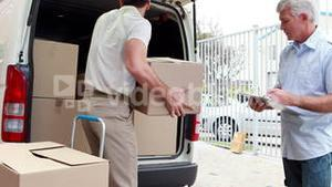 Delivery driver checking his list on clipboard with manager