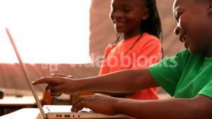 Little pupils using laptop in classroom