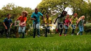 Cute pupils racing on the grass outside school