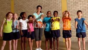 Cute pupils showing thumbs up with pe teacher