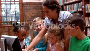 Pretty teacher using computer with pupils in library