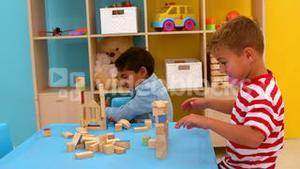 Cute little boys playing with building blocks at table in classroom