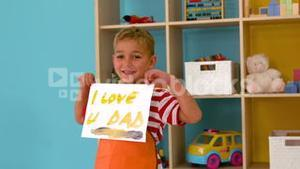 Cute little boy showing fathers day painting