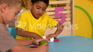 Cute little boys playing with modelling clay in classroom