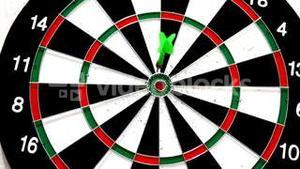 Green dart hitting the bullseye on white background