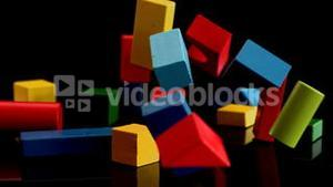 Building blocks falling and bouncing on black background