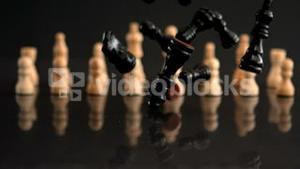 Black chess pieces falling on black background with white pieces