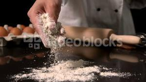 Chef sprinkling flour on black surface