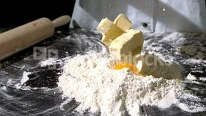 Chef adding butter to raw egg and flour on black surface