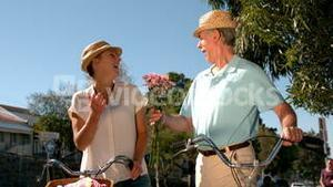 Senior couple going on a bike ride in the city with man bringing flowers
