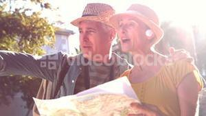 Senior couple looking at the map and pointing