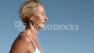 Senior woman jogging on a sunny day listening to music