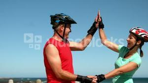 Senior couple roller blading along the pier and high fiving