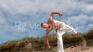 Martial arts expert practicing on the beach