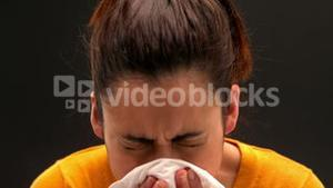 Sick young woman sneezing on black background