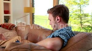 Handsome young man relaxing on his couch listening to music